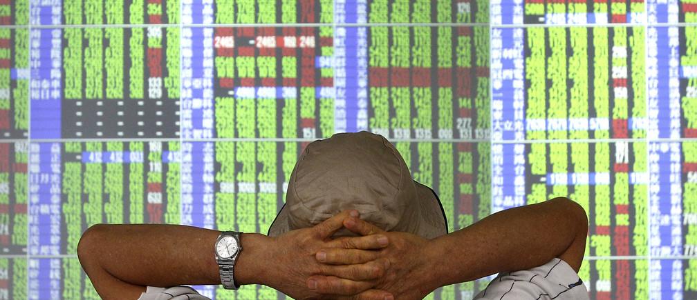 Un hombre monitorea los precios de las acciones dentro de una correduría en Taipei el 6 de septiembre de 2011.